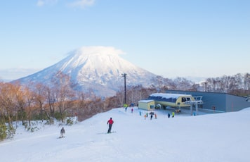 People skiing on the white snow slope with Mt.Yotei as a background in Niseko Ski area Hokkaido,Japan.